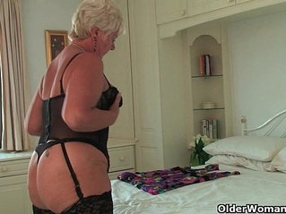 British grandma Sandie in stockings rubs her pierced clit